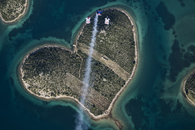 Marco Waltenspiel, Amy Chmelecki and Marco Fuerst fly with their wingsuits over the heart island