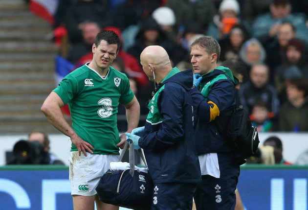 Jonathan Sexton leaves the pitch injured with Jim McShane and James Allen