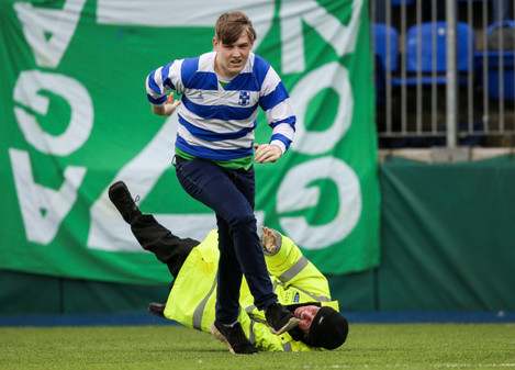 A steward falls while attempting to tackle a pitch invader