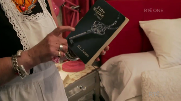 host with 50 shades of grey and the bible beside her bed