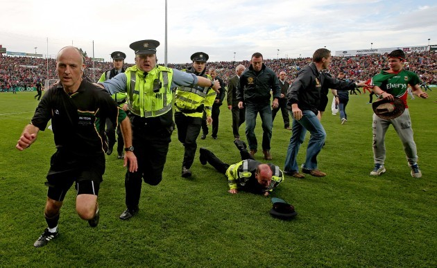 Cormac Reilly leaves the field with a garda escort after the game
