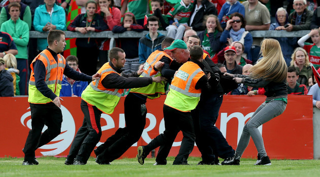A Mayo supporter is led from the pitch