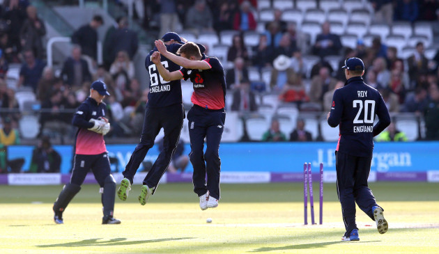 Mark Wood celebrates with a leap with Joe Root after he bowls George Dockrel to win the match