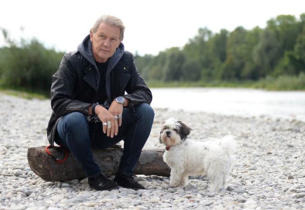 dpa-exclusive - Johnny Logan sits at Isar river with his dog