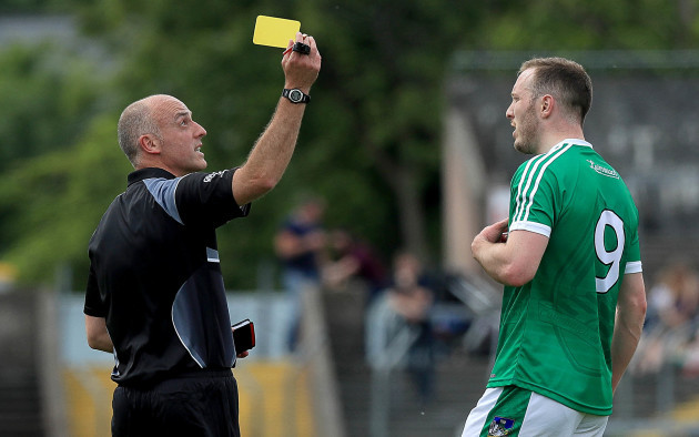 Cormac Reilly issues a yellow card to David Ward
