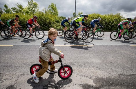 2 year old Fionn Carter tries to keep up with the peleton as they come into the town