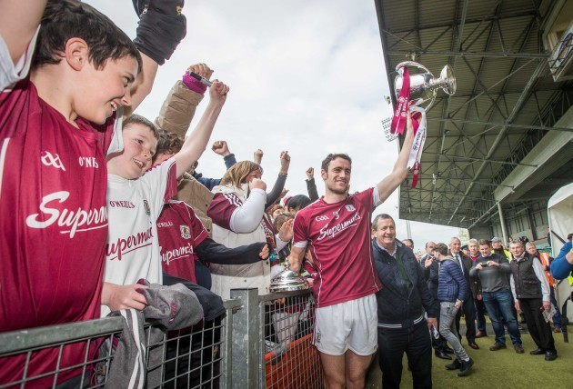 Fans celebrate with Galway captain David Burke and the Division 1 trophy
