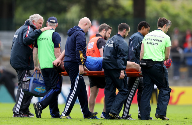 Michael Quinlivan is carried off after receiving an injury from falling awkwardly