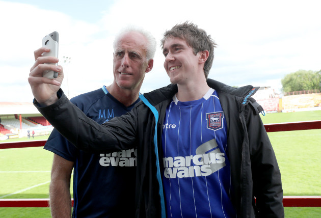 Mick McCarthy poses with a fan after the game