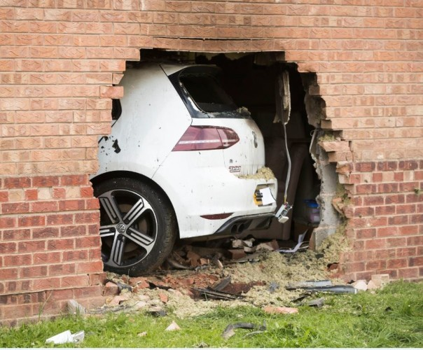 Four people injured after car crashes into house and catches fire