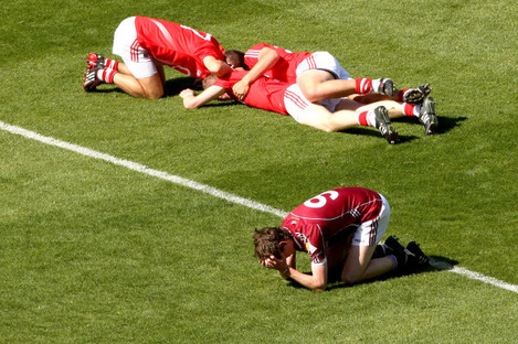 Thomas Flynn lies dejected as Jamie Wall, Jamie Burns and Luke O'Connolly celebrate