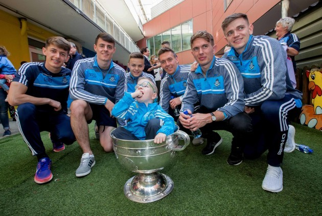 Liam Collins sits in the Sam Maguire with Evan Comerford, Brian Howard, Eoin Murchan, Mark Schutte, Michael Ftizsimons and Cillian O'Shea