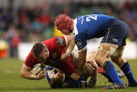 Munster's Dave Kilcoyne is tackled by Leinster's Garry Ringrose and  Josh Van der Flier