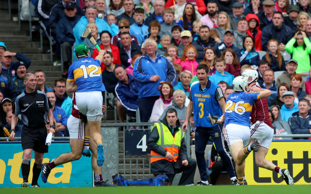 Joe Canning scores the winning point despite Noel McGrath and Niall O'Meara
