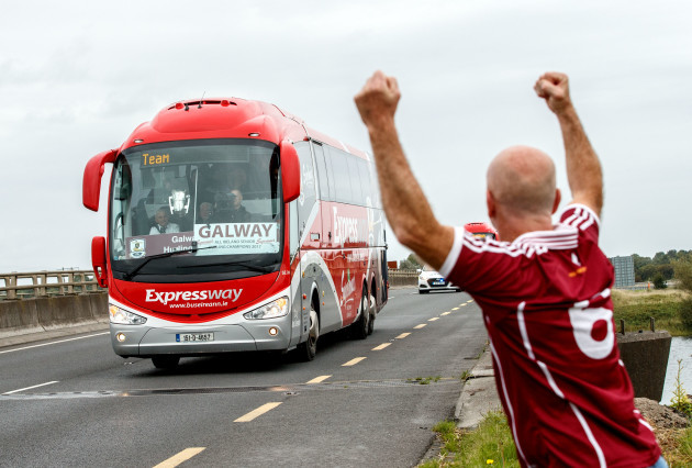 The Galway team bus with the Liam McCarthy Cup pass over the River Shannon as Timmy O Flatharta salutes the team