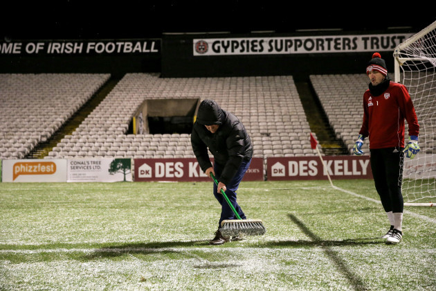 A member of the ground staff clears snow from the pitch