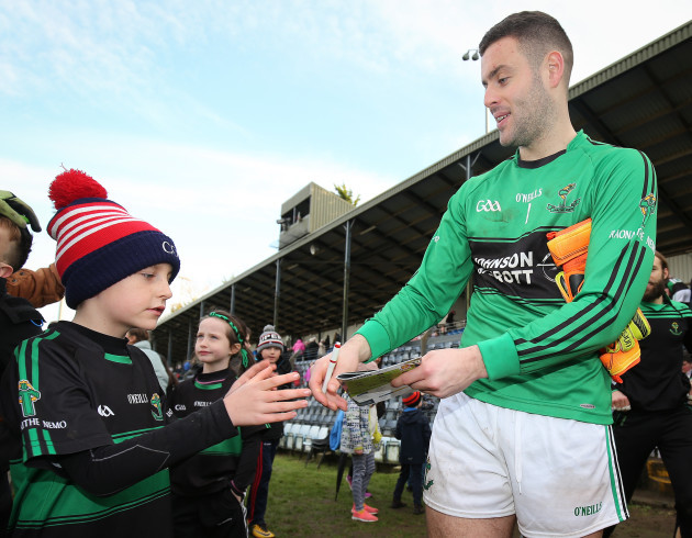 Micheal Aodh Martin signs a programme for a young fan after the game