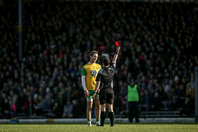 Paddy Neilan shows Nathan Mullins a red card