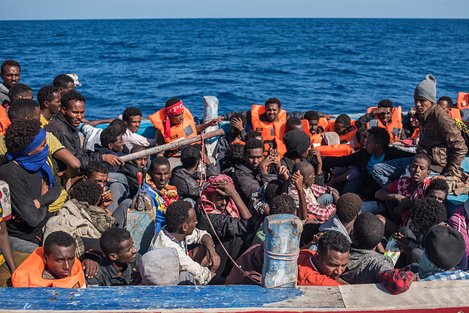 Migrants seen packed in their boat crossing the ocean into