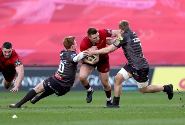 Rory Scannell is tackled by Rhys Patchell and James Davies