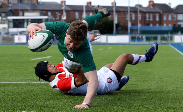 Hugh Lane scores a try despite the efforts from Seung Sin Lee
