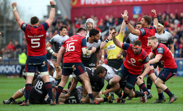 Munster players celebrate as referee Nigel Owens awards a penalty to finish the game
