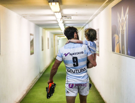 Maxime Machenaud walks down towards the dressing room with his son Gaspard after the game