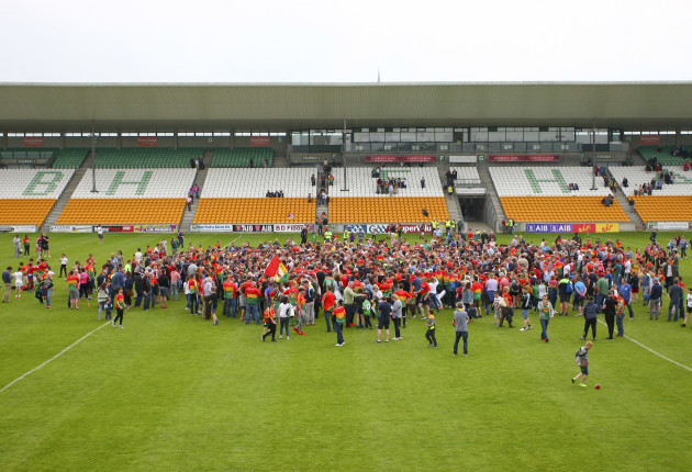 Carlow supporters celebrate on the pitch after the game