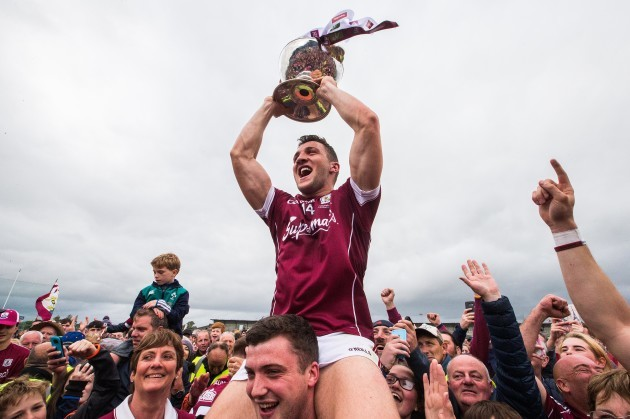 Damien Comer celebrates after the game with the trophy