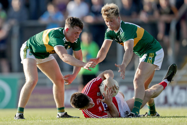Tadhg Corkery tackled by Dara Moynihan and Fiachra Clifford