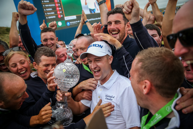 Russell Knox celebrates with green keepers on the 18th green