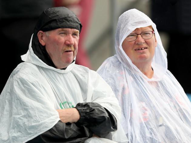 Spectators during a downpour