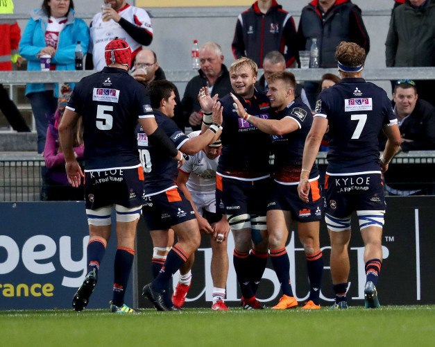 Tom Brown celebrates scoring a try with teammates