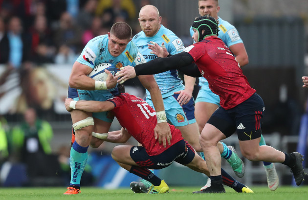 Exeter Chief's Dave Ewers is tackled by Munster's Joey Carbery and Chris Cloete