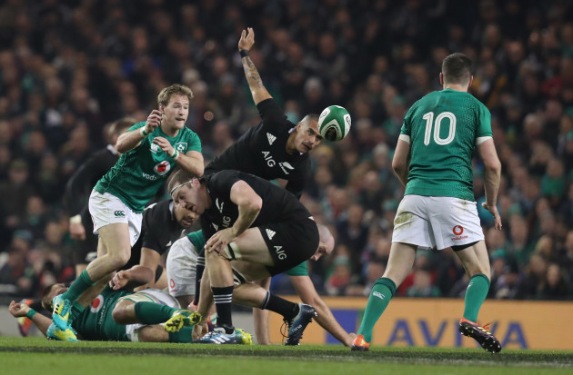 Ireland's Kieran Marmion passes to Jonathan Sexton as New Zealand's Aaron Smith and Brodie Retallick look on