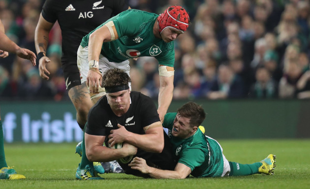 New Zealand's Scott Barrett is tackled by Ireland's Josh van der Flier and Luke McGrath