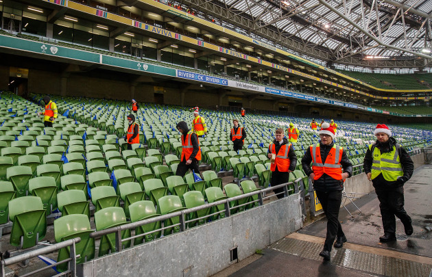 Stewards wearing Christmas hats perform final checks before the game