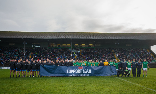 Both teams hold up a sign in support of Sean Cox before the game