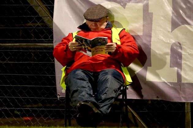 Steward Dan Cronin reading the match program