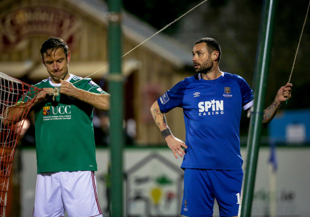 Alan Bennett and Damien Delaney fix the goal net during the game