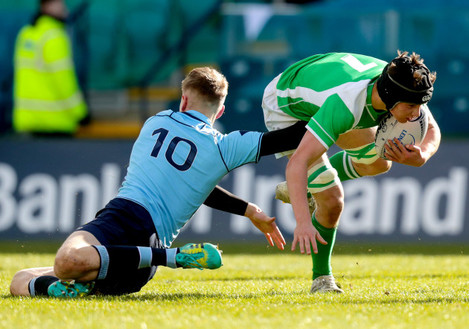Tom Cullen is tackled by Niall Carroll