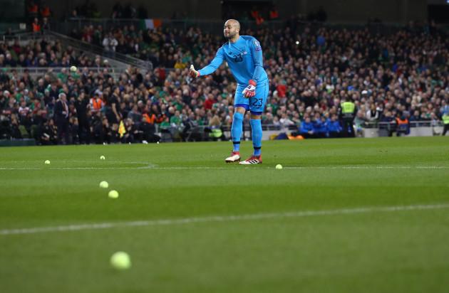 Darren Randolph removes tennis balls from the field