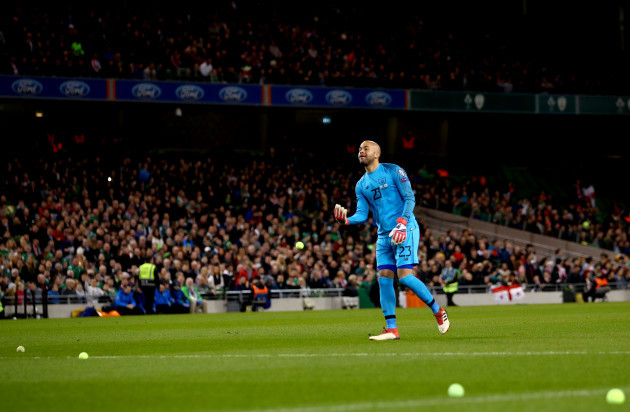 Darren Randolph removes tennis balls from the field
