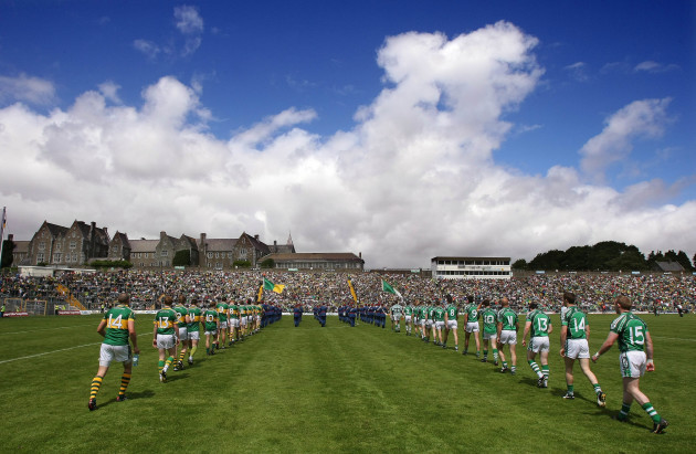 The Kerry and Limerick players walk behind the band