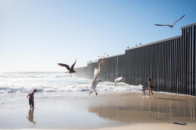 Migrants crossing the US-Mexico border wall in Tijuana, Mexico - 13 Mar 2019