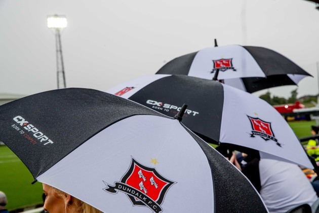 Dundalk fans shelter from the rain before the game