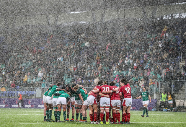 a-view-of-the-ireland-and-wales-teams-in-a-huddle-during-the-tough-weather-conditions
