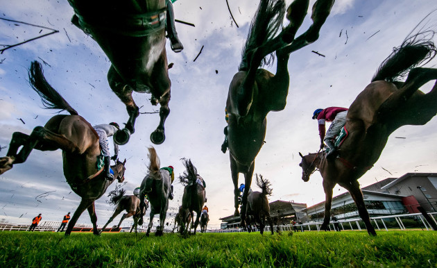 a-general-view-of-the-runners-and-riders-as-they-clear-a-fence-in-the-paddy-power-steeplechase