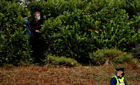 local-spectators-look-on-in-between-the-bushes