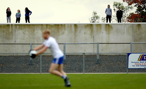 local-spectators-look-on-from-outside-the-ground